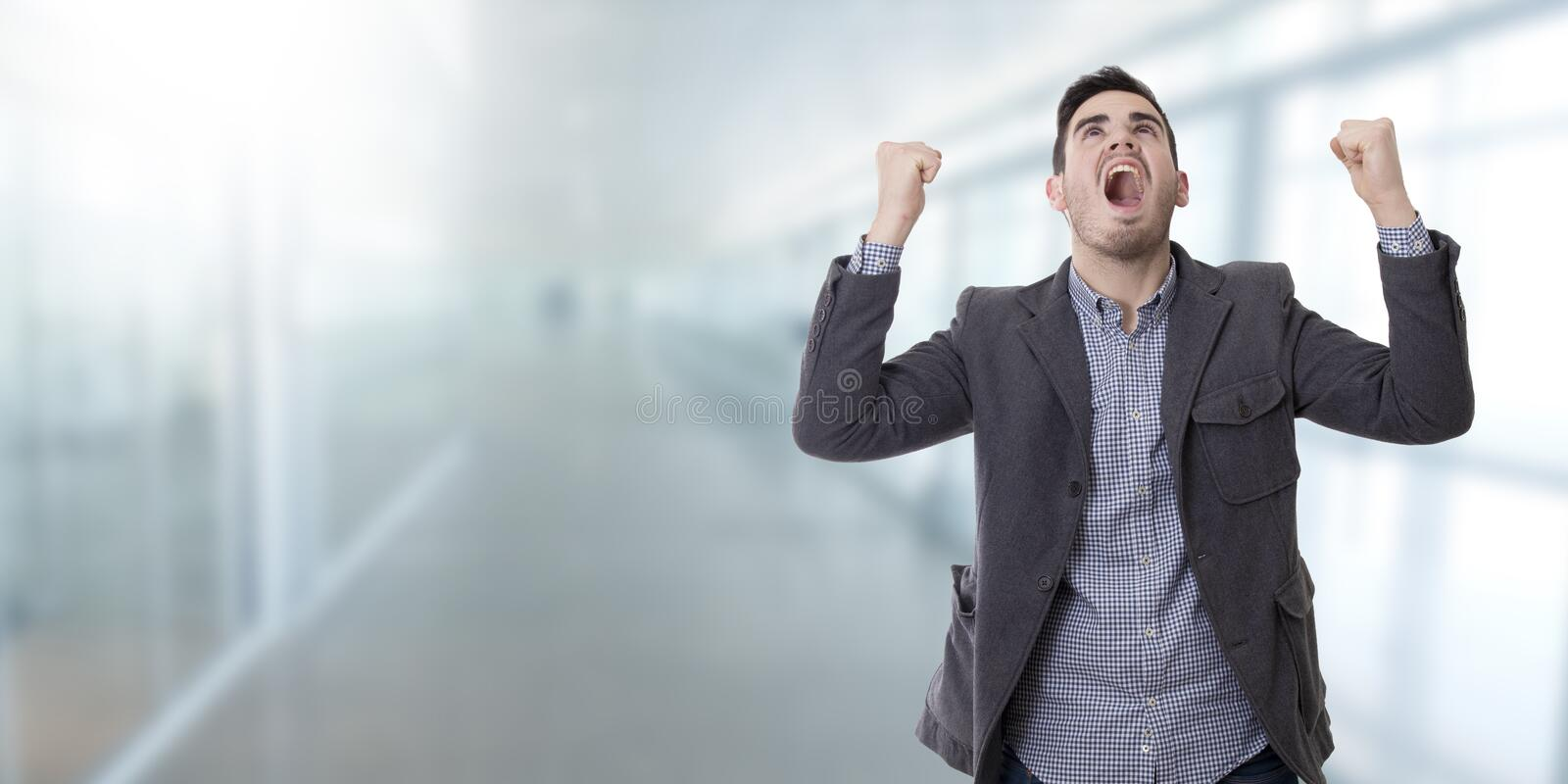 Man shouting enraged. Adult young man shouting enraged with the arms raised royalty free stock photography