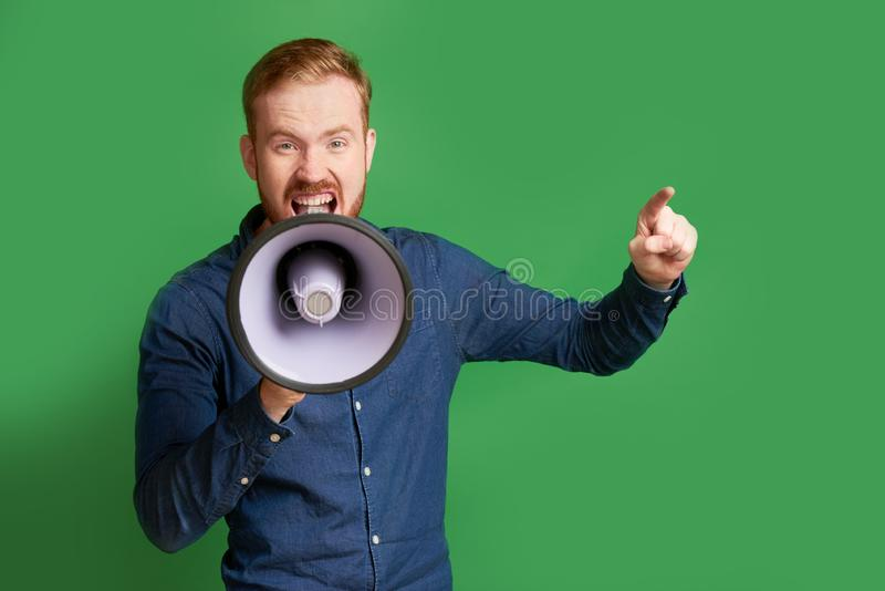 Man shouting in megaphone. Excited emotional young man shouting motto in megaphone royalty free stock photos