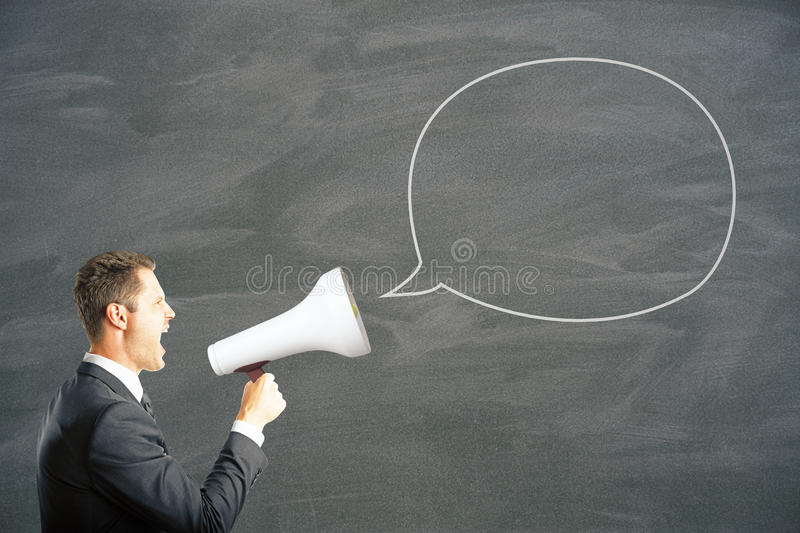 Man shouting into megaphone. Speech bubble and caucasian businessman shouting into megaphone. Mock up stock images