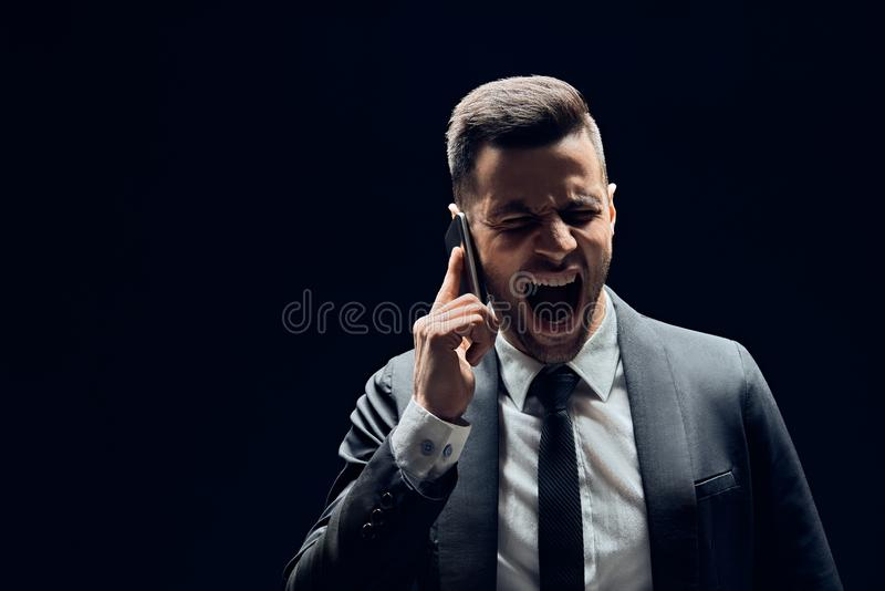 Man shouting on mobile phone with copy space isolated on dark background royalty free stock image
