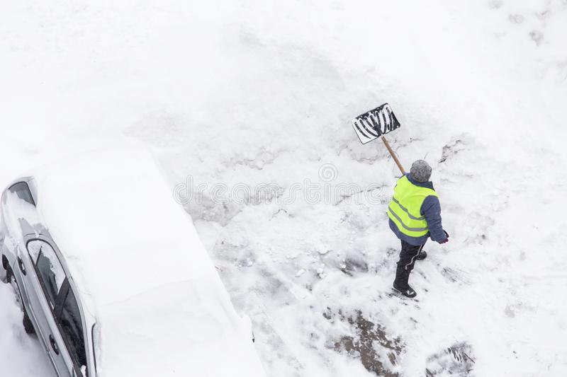 Man shoveling snow after snowfall and blizzard, copy space. Top view royalty free stock image