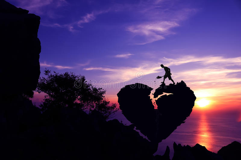 Man shoveling stone to repair the broken heart shape rock on the mountain. Man shoveling stone to repair the broken heart shape rock on the mountain with purple stock photography