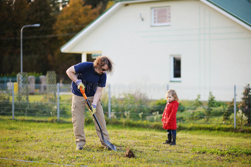 A man shovels a hole in the yard