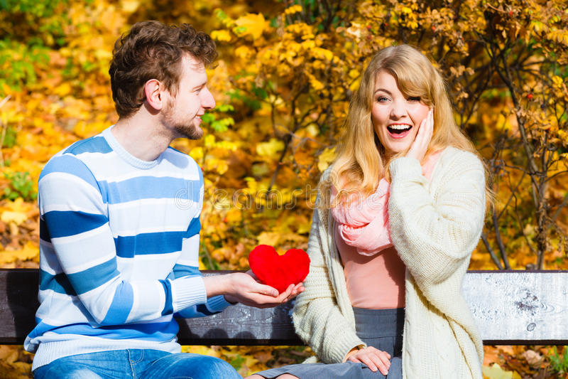 Man show feelings to girl in autumnal park. Accepting and sharing feelings. Confessing love and affection with romantic gesture. Positive reaction. Pair sit on stock photography