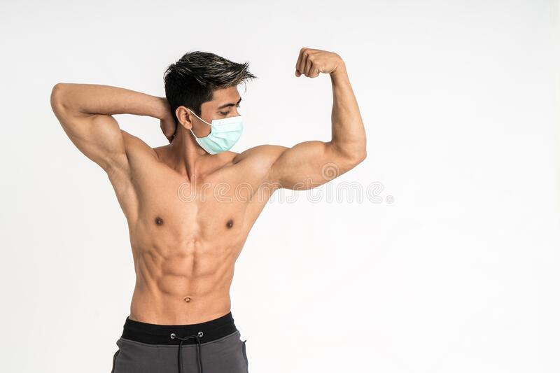 Man show muscular biceps wearing a mask stand facing forward and look to side stock photos