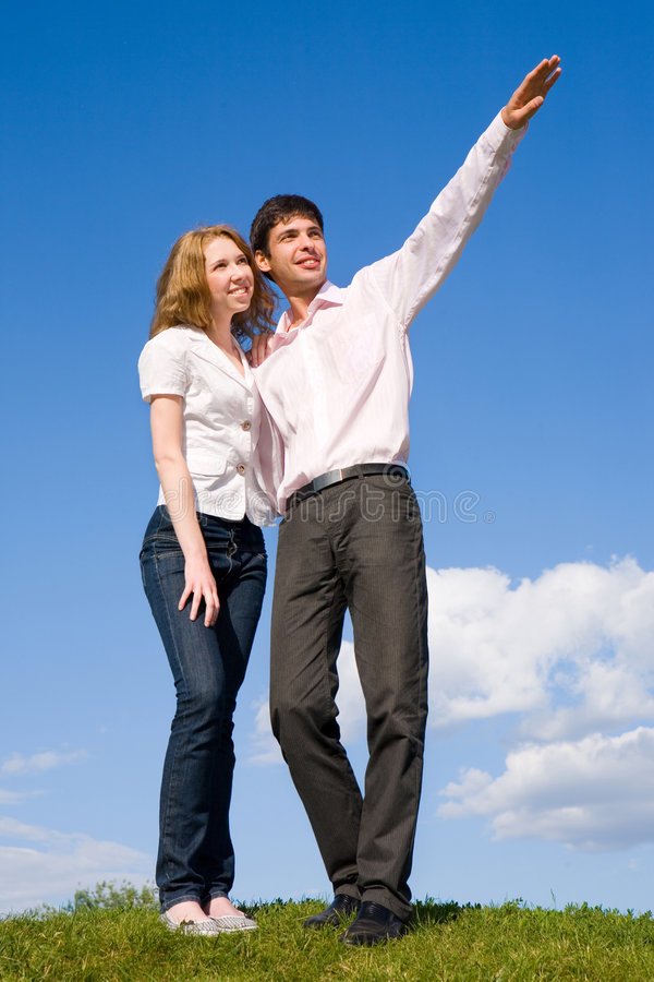 Man show something by hand. Happy young couple looking at something above a green meadow. Man show something by hand stock image