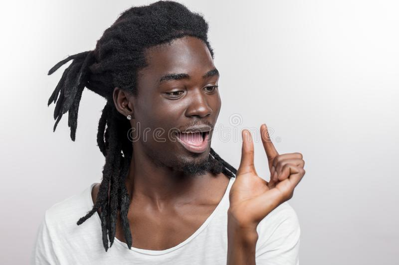 Dark skinned man showing small thing while smiling and standing near white background royalty free stock photos