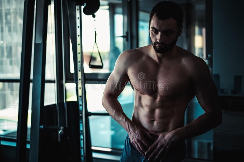 Man showing abs in the gym stock photos