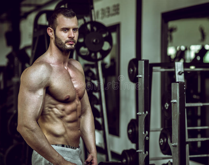 Man showing abs in gym. Man posing in gym showing abs stock images
