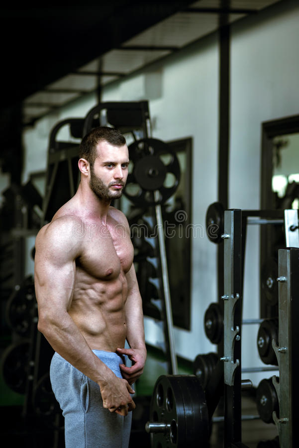 Man showing abs in gym stock image