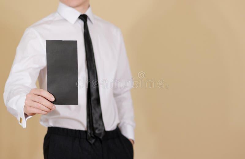 Man showing blank black flyer brochure booklet. Leaflet presentation. Pamphlet hold hands. Man show clear offset paper. Sheet. Template. Booklet design sheet royalty free stock photos