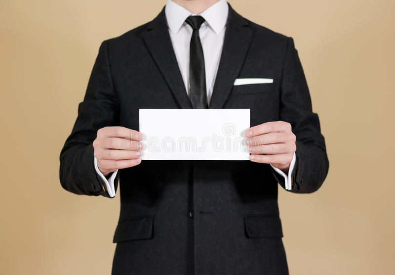 Man showing blank black flyer brochure booklet. Leaflet presentation. Pamphlet hold hands. Man show clear offset paper. Sheet. Template. Man in a black suit royalty free stock image