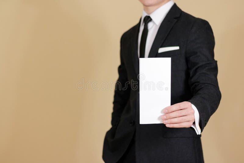 Man showing blank black flyer brochure booklet. Leaflet presentation. Pamphlet hold hands. Man show clear offset paper. Sheet. Template. Man in a black suit stock photo