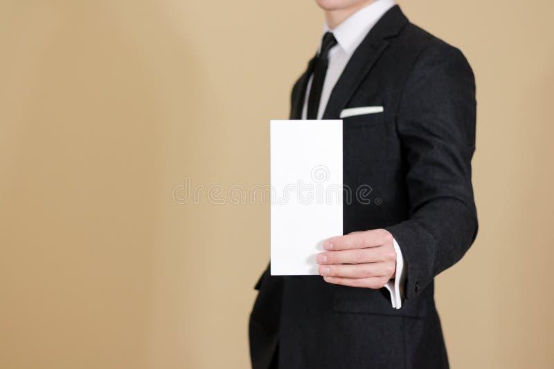 Man showing blank black flyer brochure booklet. Leaflet presentation. Pamphlet hold hands. Man show clear offset paper. Sheet. Template. Man in a black suit stock images