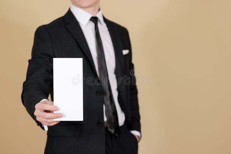 Man showing blank black flyer brochure booklet. Leaflet presentation. Pamphlet hold hands. Man show clear offset paper. Sheet. Template. Man in a black suit stock photos