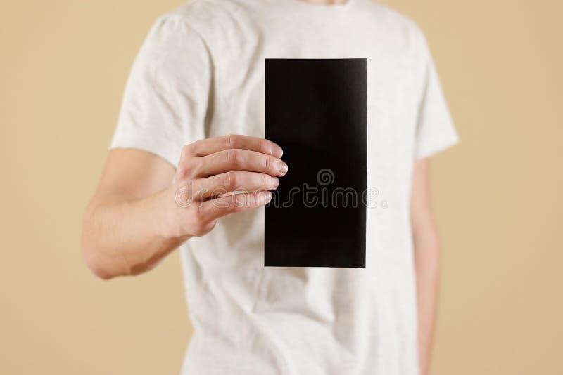 Man showing blank black flyer brochure booklet. Leaflet presentation. Pamphlet hold hands. Man show clear offset paper. Sheet. Template. Booklet design sheet stock photography