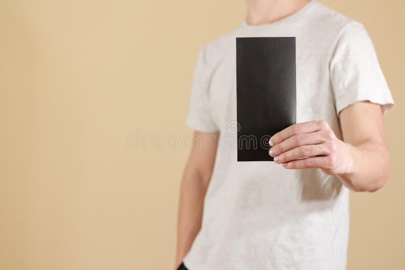 Man showing blank black flyer brochure booklet. Leaflet presentation. Pamphlet hold hands. Man show clear offset paper. Sheet. Template. Booklet design sheet stock images