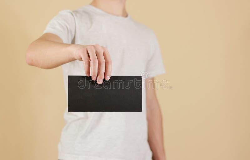 Man showing blank black flyer brochure booklet. Leaflet presentation. Pamphlet hold hands. Man show clear offset paper. Sheet. Template. Booklet design sheet stock image
