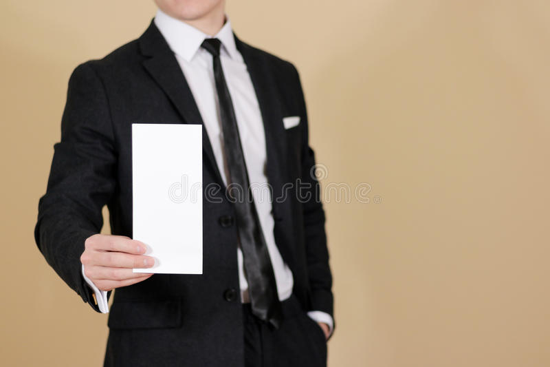 Man showing blank black flyer brochure booklet. Leaflet presentation. Pamphlet hold hands. Man show clear offset paper. Sheet. Template. Man in a black suit royalty free stock photos