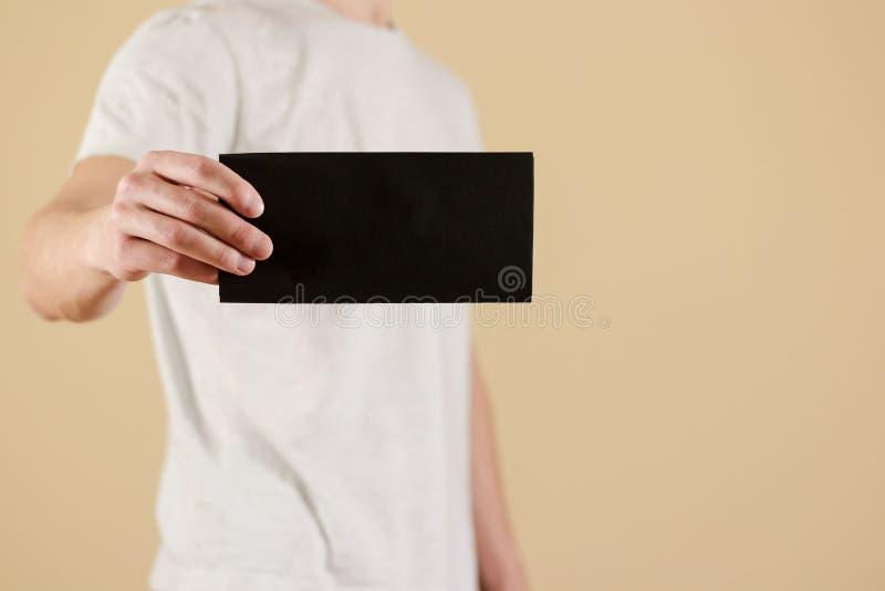 Man showing blank black flyer brochure booklet. Leaflet presentation. Pamphlet hold hands. Man show clear offset paper. Sheet. Template. Booklet design sheet royalty free stock images