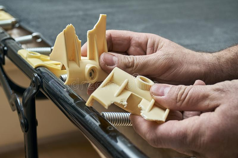 Man showing broken plastic bed slat holders. Just unscrewed from a folding bed royalty free stock image