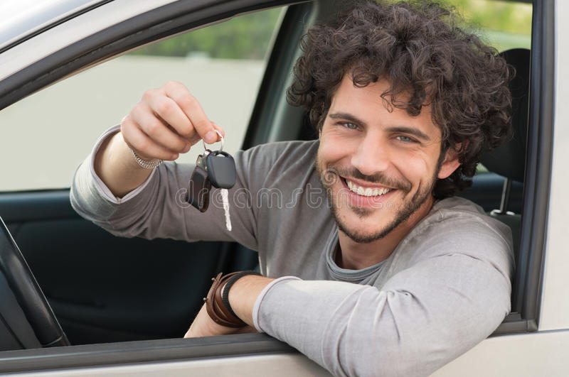 Man Showing Car Key. Portrait Of Young Happy Man Showing The Key Sitting In New Car royalty free stock photo