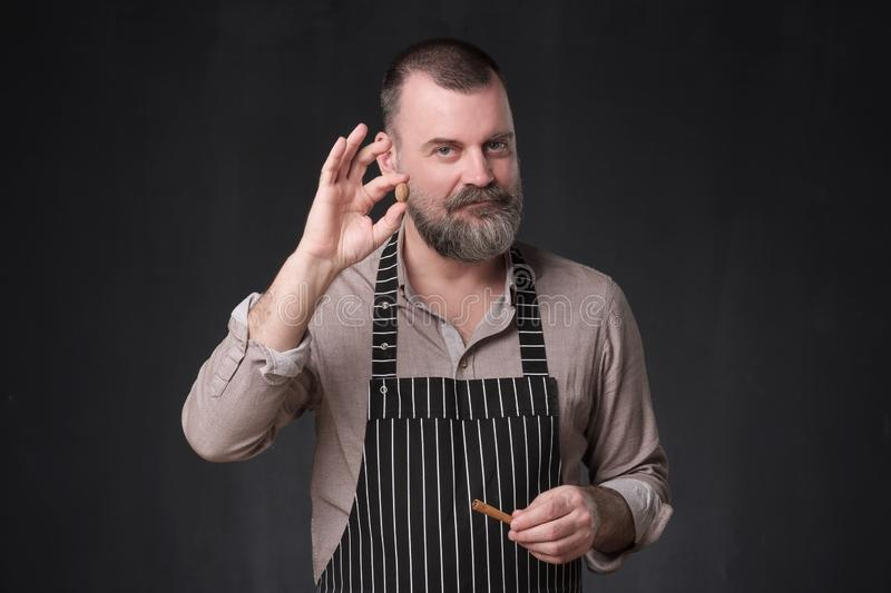 Man showing cinnamon spices. Advice how to cook. stock images