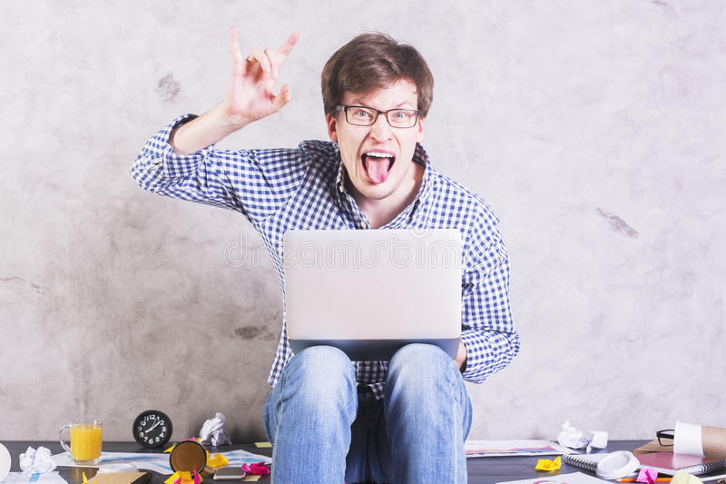 Man showing devil's horns. Crazy man with laptop sitting on messy office desktop and showing devil's horns sign royalty free stock images