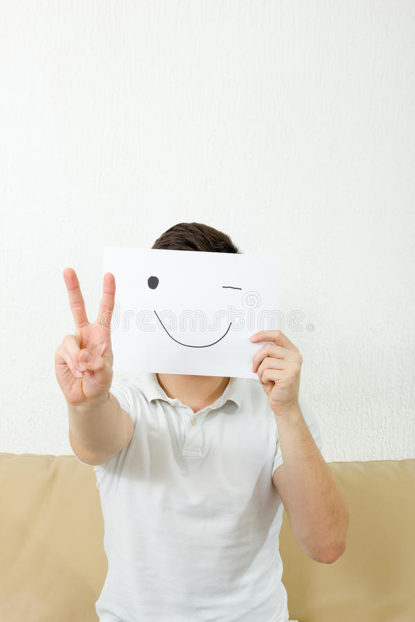 Man showing 2 fingers. Victory hand sign, number. Concept photo of peace symbol. Adult boy cover his face with happy wink smile drawn on paper.Fanny crazy royalty free stock photo