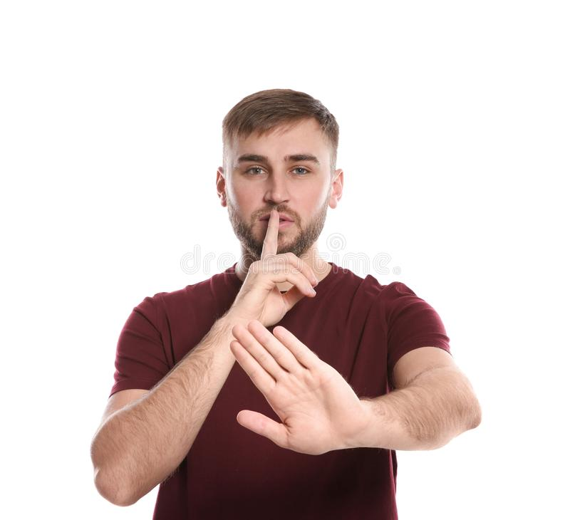 Man showing HUSH gesture in sign language on white stock photos