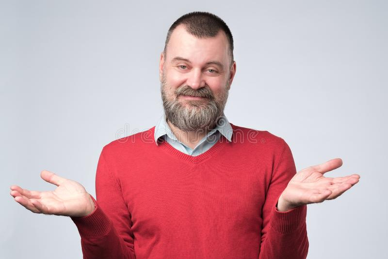 Man showing I have no idea gesture, shrugging shoulders and raising hands. Confused handsome man in red sweater showing I have no idea gesture, shrugging royalty free stock photos