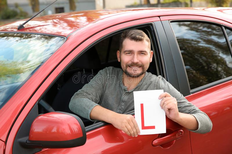 Man showing learner driver sign from new car. Get driving license royalty free stock photography
