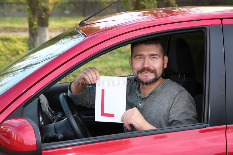Man showing learner driver sign from new car. Get driving license stock photography