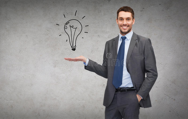 Man Showing Light Bulb On The Palm Of His Hand Stock Photo