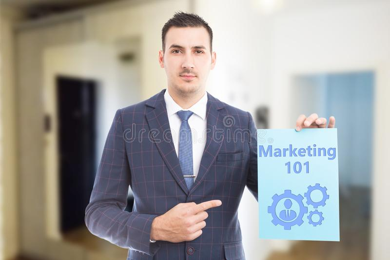 Man showing marketing must-know with drawing. Man wearing suit and tie showing marketing must-know with mechanism and person drawing on blue paper as learning stock photography
