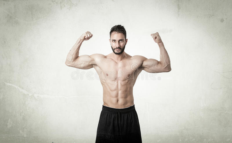Man showing muscles in abstract room stock photography
