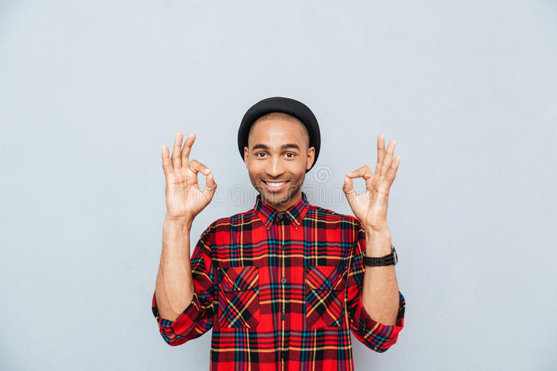 Man showing ok sign. Cheerful attractive african young man showing ok sign stock photography