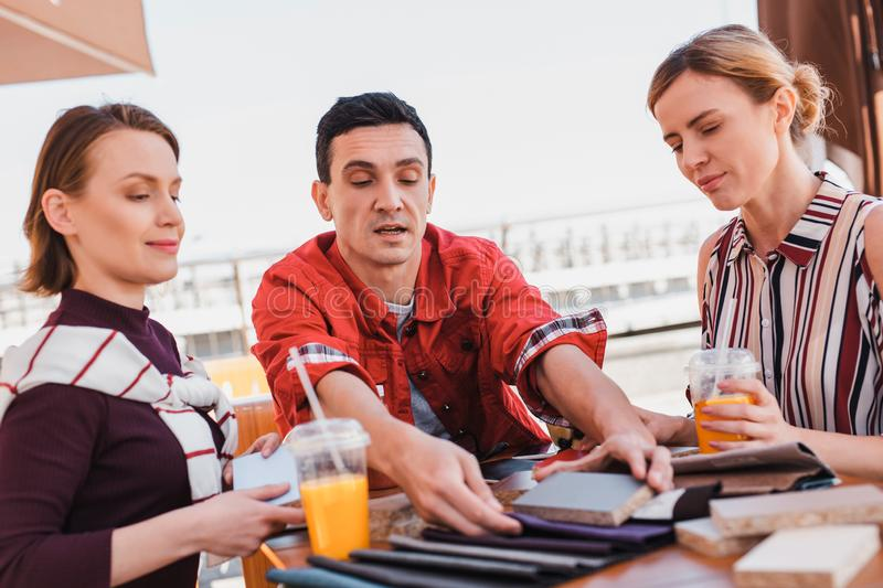 Man showing samples of materials to customers during the lunch stock image