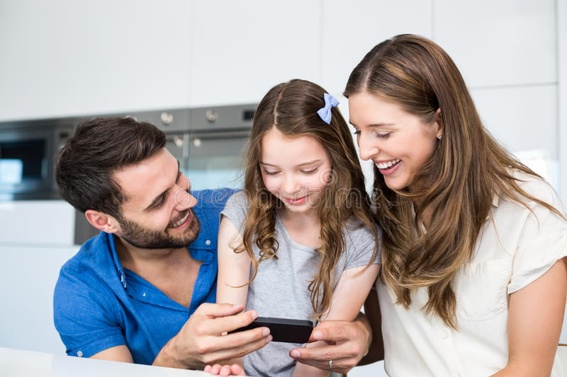 Man showing smart phone to family. At home royalty free stock photography