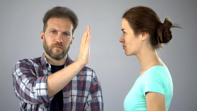 Man showing stop sign to annoyed wife who constantly screaming and complaining stock images
