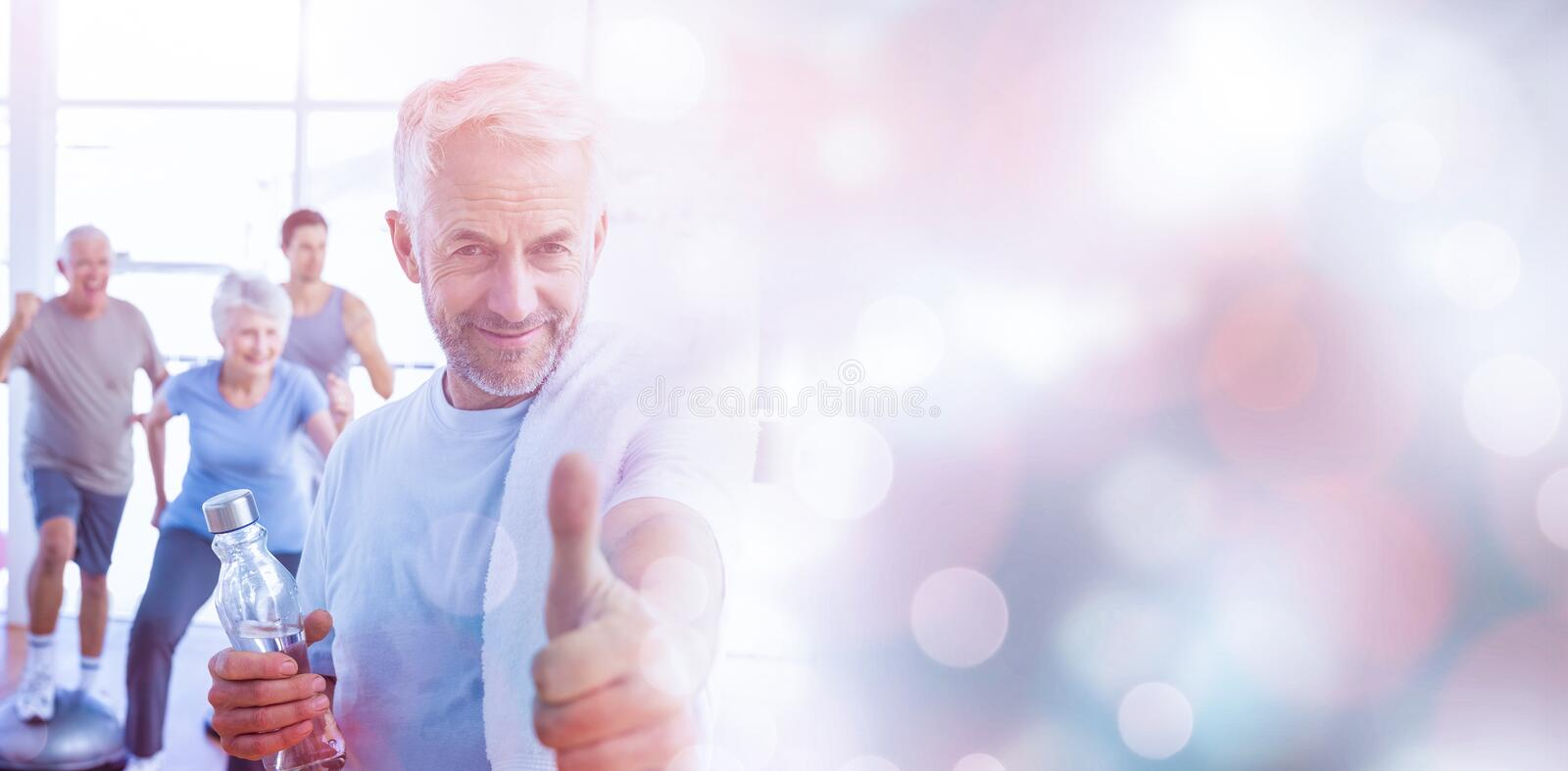 Man showing thumbs up sign with people exercising in background royalty free stock photography