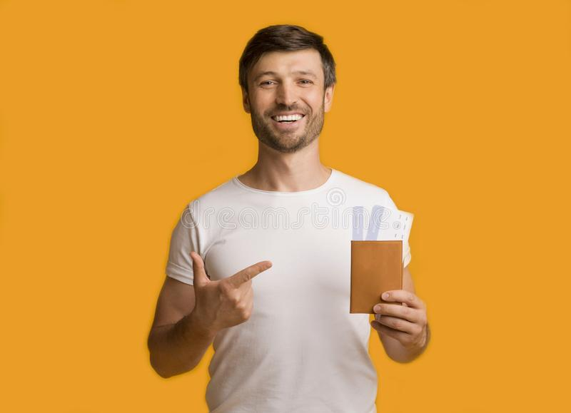 Man Showing Tickets And Passport Pointing Finger Standing, Studio Shot royalty free stock photos