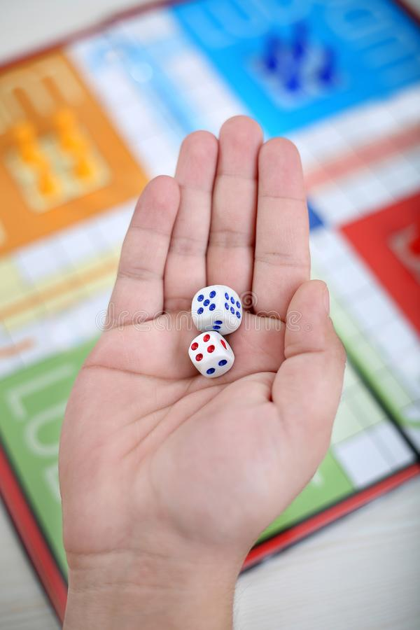 Man is showing two dice in hand stock photography