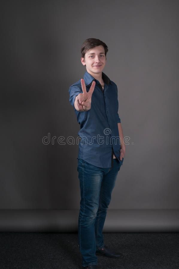 Man showing victory sign with fingers, smiling and looking at camera. Handsome young man with dark hair in blue shirt standing, holding hand in pocket, showing stock image