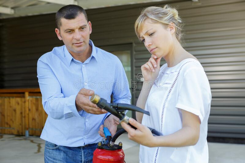 Man showing woman how to use fire extinguisher royalty free stock photography