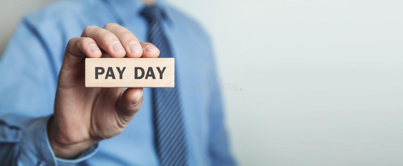 Man showing wooden block. Pay Day. Business concept stock photo