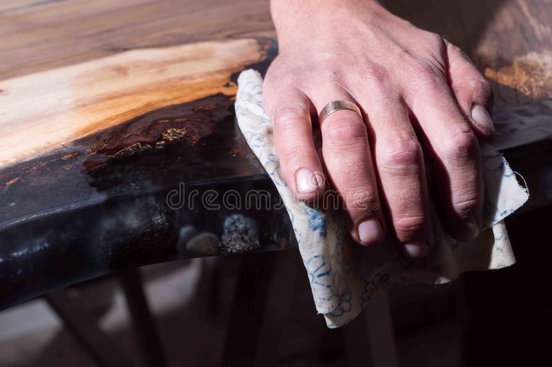 Man shows the difference wet tree and dry. black resin with stones inside. royalty free stock images
