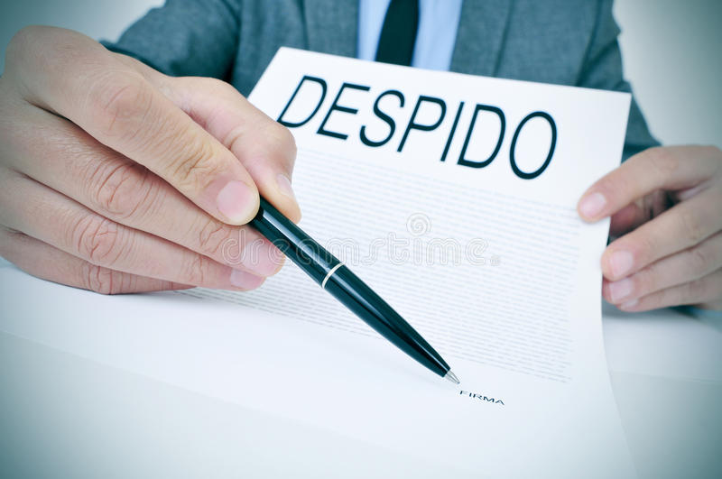 Man shows a document with the text despido, dismissal in spanish. A young caucasian businessman sitting at his office desk shows a document with the word despido royalty free stock photography