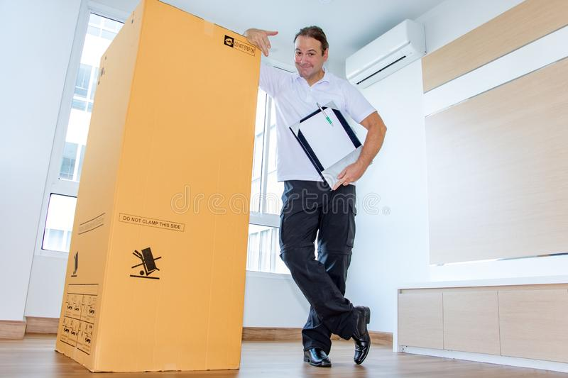 A man shows a large package in an empty room. The postman delivers the parcel to the new apartment stock image