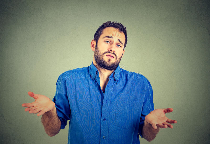 Man shrugging shoulders who cares so what I don't know gesture. Ignorance and arrogance. Closeup portrait young man shrugging shoulders who cares so what I don't royalty free stock photo